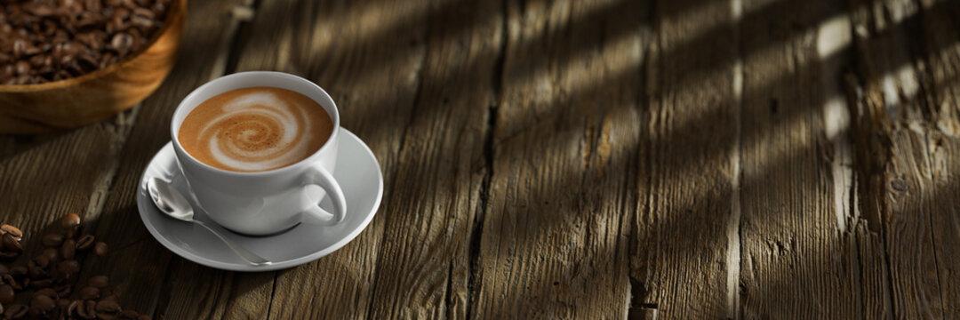 Frische Tasse Kaffee auf Tisch aus Holz mit Kaffeebohnen