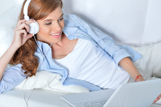 Portrait of young woman listening music with headphones in bed at home