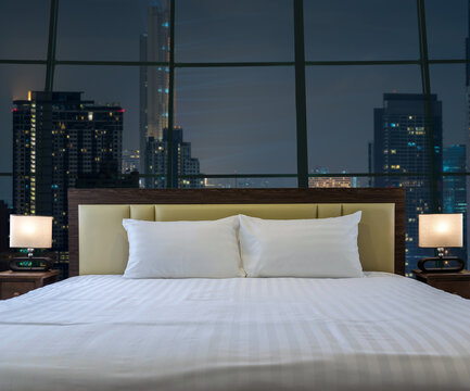 Luxury Interior bedroom with windows glass beside Top view of Bangkok Cityscape at night, Mahanakhon, relax and holiday concept, celebration in happy new year and merry christmas concept