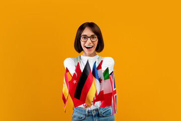 Foreign language studying school concept. Excited lady showing bunch of diverse flags, posing over...