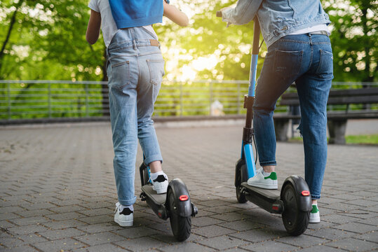 Mother and daughter riding electric scooters