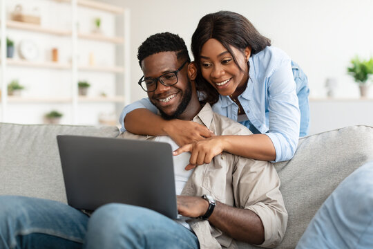 Portrait of African American couple using computer pointing at screen