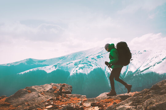 Amazing landscape with snowy mountains range and hiker with backpack on a foreground. Travel and adventure concept