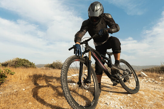 Downhill rider fully equipped with protective gear and his bicycle