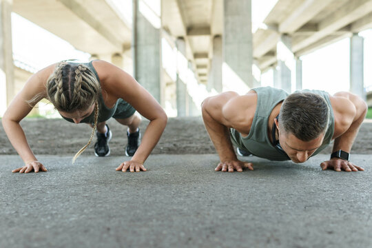 Athletic couple and fitness training outdoors. Man and woman doing push-ups exercise.