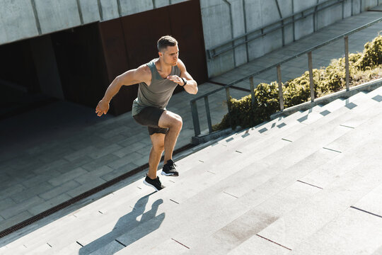 Athletic man is running upstairs by concrete staircase outdoors