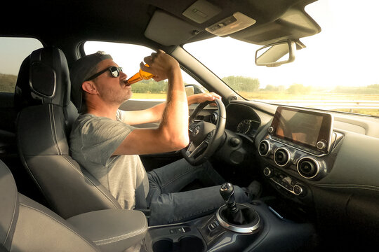 Man drive a car and drink a beer. Driver young male drinking alcoholic beverage while driving. Dangerous behavior, drunk guy, accident risk. Danger, transgression, risky, distraction concept.