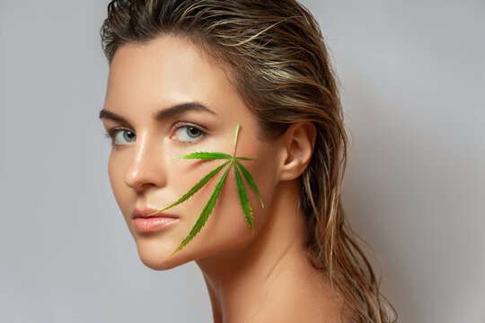 CBD cosmetics concept. Beautiful woman with a cannabis leaf