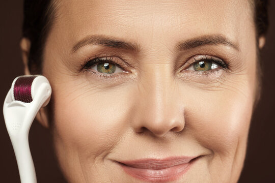 Middle aged woman using mesoroller for her facial skin.