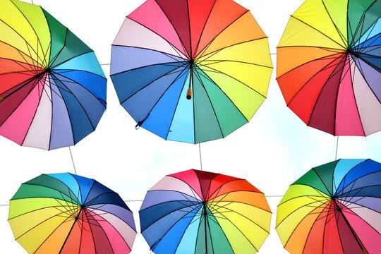 Bunte Regenbogen Sonnenschirme. Die Regenbogenfarben stehen als Symbol für die Akzeptanz und Gleichberechtigung von menschen die eine andere Sexualität leben als die Hetrosexualität. LGBT LSBTI LGBT
