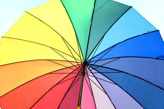 Bunter Regenbogen Sonnenschirm. Die Regenbogenfarben stehen als Symbol für die Akzeptanz und Gleichberechtigung von menschen die eine andere Sexualität leben als die Hetrosexualität. LGBT LSBTI LGBT