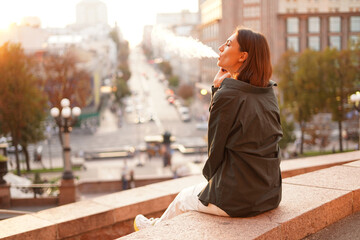 Fototapeta Woman at sunset with amazing city view, enjoying warm days, freedom, positive vibes, smoking  electronic cigarette obraz