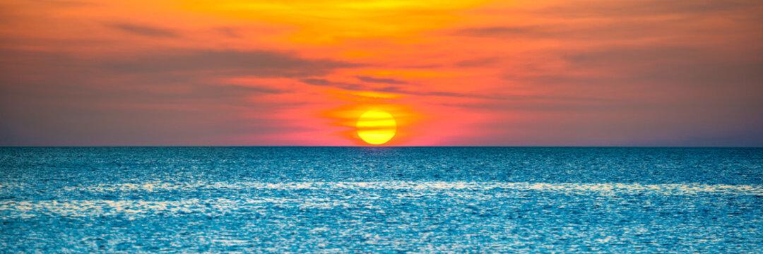 Panorama of nature landscape with beautiful dramatic orange sunset over blue rippled sea