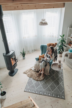 Remote work. Young woman using laptop in a cozy armchair and plaid sitting by the fireplace with a domestic cat, drinking tea at home