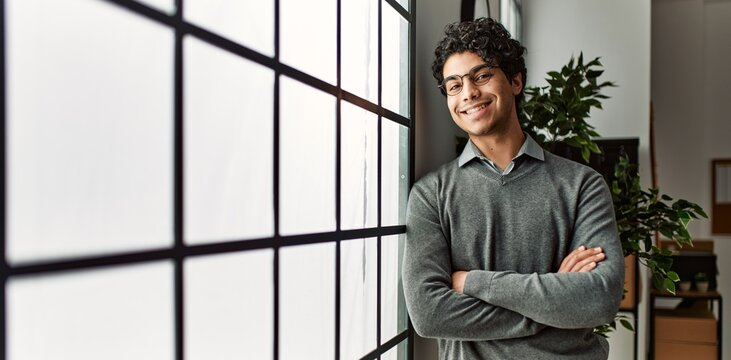 Young hispanic businessman smiling happy standing with arms crossed gesture at the office.