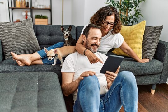 Middle age hispanic couple smiling happy and using touchpad. Sitting on the sofa with dogs at home.