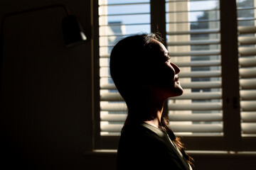 Asian woman sitting standing in ray of light at window