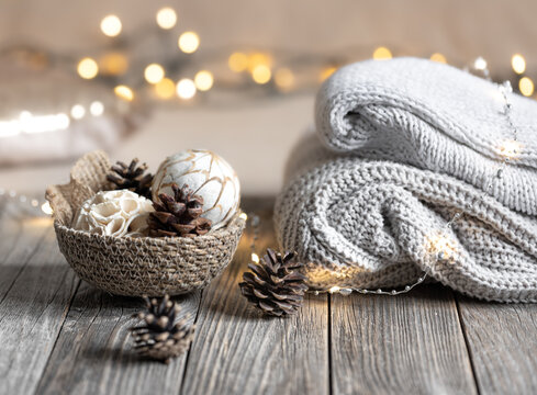 Cozy winter bokeh background with stacked sweaters and decor details.