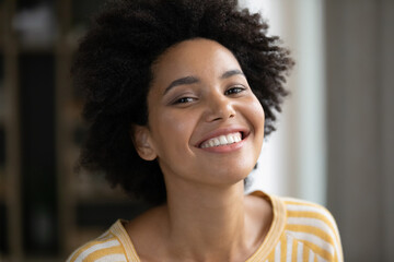 Fototapeta Head shot happy beautiful african american woman looking at camera. Joyful millennial mixed race female client with white toothy smile and perfect skin satisfied with dentistry or cosmetology service. obraz