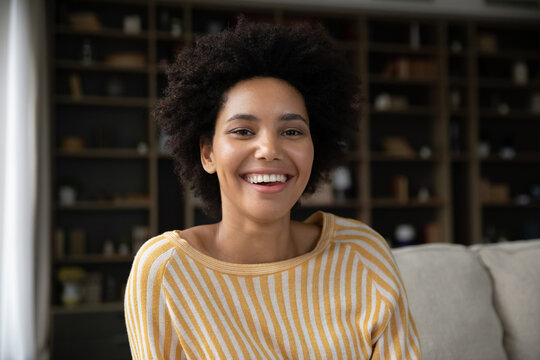 Happy young african american woman sitting on couch, looking at camera, enjoying video call meeting with friends. Professional biracial female blogger streaming in social network online, webcam view.