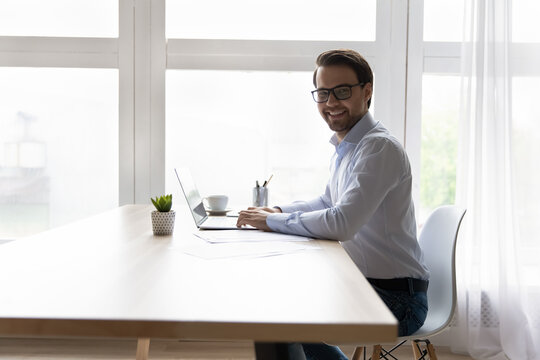 Portrait smiling businessman in glasses sitting at desk with laptop home office workplace, working online, happy successful man entrepreneur freelancer looking at camera, posing for picture