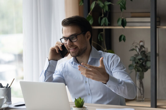 Smiling businessman in glasses talking on phone, explaining, enjoying pleasant conversation, sitting at home office desk with laptop, friendly manager entrepreneur consulting client by cellphone call
