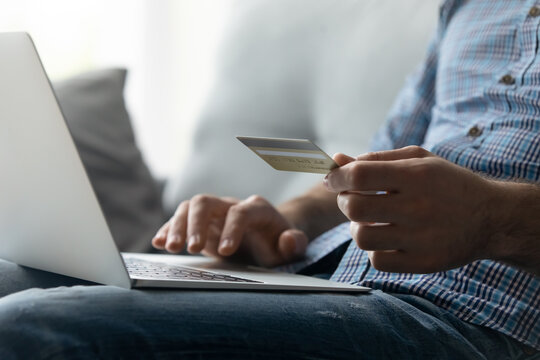 Crop close up man purchasing goods or paying domestic bills online by credit card, using laptop, typing entering information, young male customer making secure internet payment, shopping at home