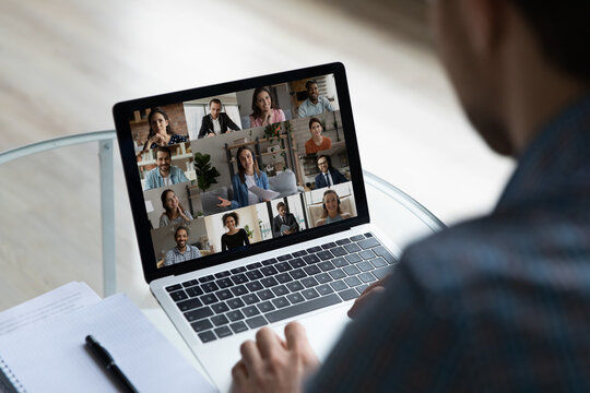 View over businessman shoulder group video call on laptop screen, diverse colleagues business partners chatting online, engaged in internet conference, meeting by webcam, distance work concept