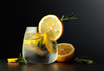Fototapeta Cocktail gin-tonic with lemon slices and twigs of rosemary on a black background. obraz