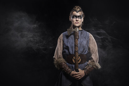 Woman viking warrior in history costume with ax on dark background