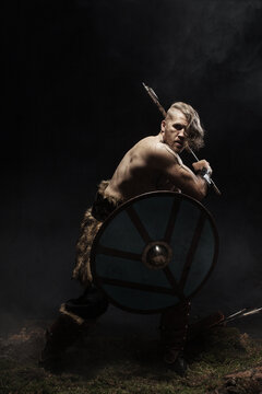 Viking warrior in full with ax aggressively attacks on dark background