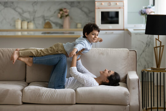 Happy young indian mother lifting in air on straight arms joyful cute small child son, lying on cozy couch. Joyful asian family practicing balance doing yoga exercises, having fun playing at home.