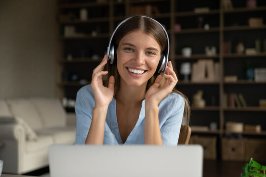 Happy millennial girl wearing headphones, looking at camera over laptop, smiling. Young distance employee, student, female blogger, coach, teacher giving consultation. Head shot video call portrait