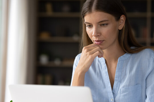 Serious young office worker thinking over work project task, sitting at laptop, looking at screen, reading, touching chin. Millennial student using online virtual app on computer, chatting on Internet