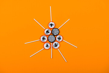 Halloween candy with black spiders and cobweb on orange color background,top view