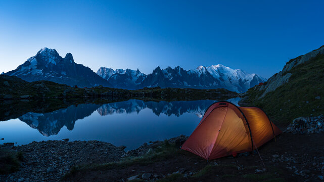 Red tent at Lac des Cheserys in the mountains near Chamonix during blue hour.