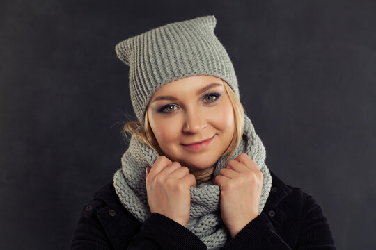 Happy woman in gray knitted hat on black background