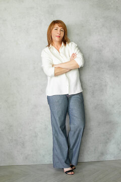Confident middle aged business woman with crossed arms standing on grey background