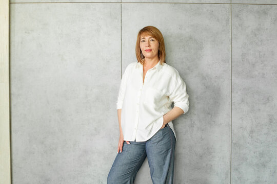 Happy successful mature business woman standing on gray background portrait