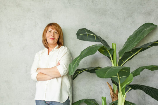 Cheerful middle aged woman with redhead hair with green plant