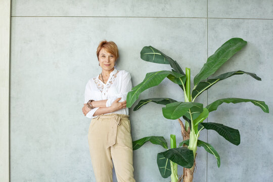 Mature businesswoman working in modern office with green plants