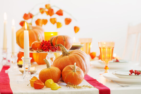 autumn table setting with burning candles and pumpkins
