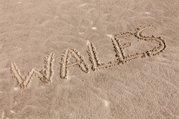Fototapeta Wales texture writing background of handwritten text in sand on a Welsh seaside beach at a summer holiday travel destination resort, stock photo image obraz