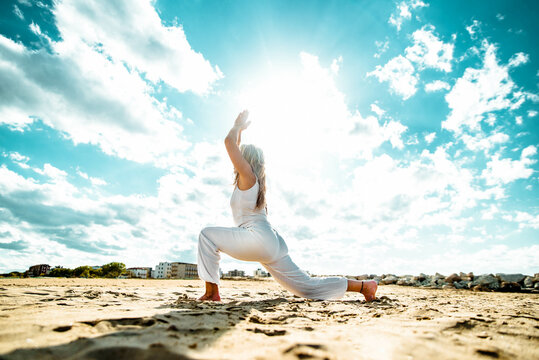Senior woman doing yoga exercise tree pose at beach - Calm and meditation concept