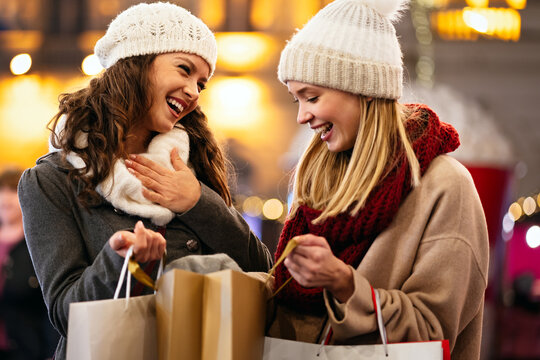 Happy women friends are shopping for presents at Christmas. People holiday sale shopping concept
