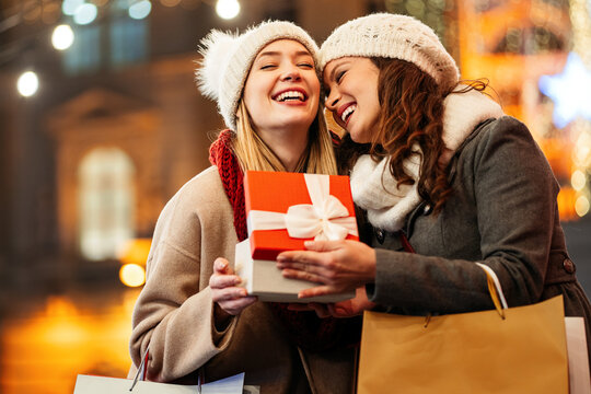 Happy women friends exchanging christmas present. Happiness people friend shopping xmas concept