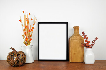 Fototapeta Mock up black frame with autumn branches and decor on a wood shelf. Fall concept. Portrait frame against a white wall. Copy space. obraz