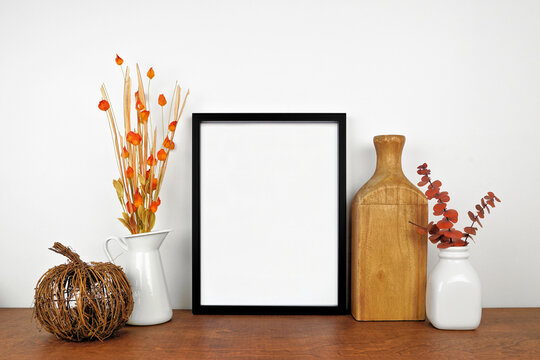 Mock up black frame with autumn branches and decor on a wood shelf. Fall concept. Portrait frame against a white wall. Copy space.