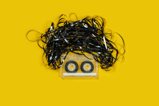 Audio cassette with tape forming a face with eyes and hair