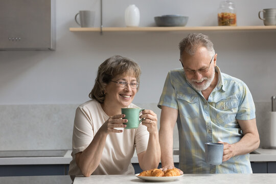 Happy middle aged mature retired married couple drinking hot morning coffee or tea, eating fresh croissants, enjoying communicating during weekend breakfast in modern kitchen, family relations concept
